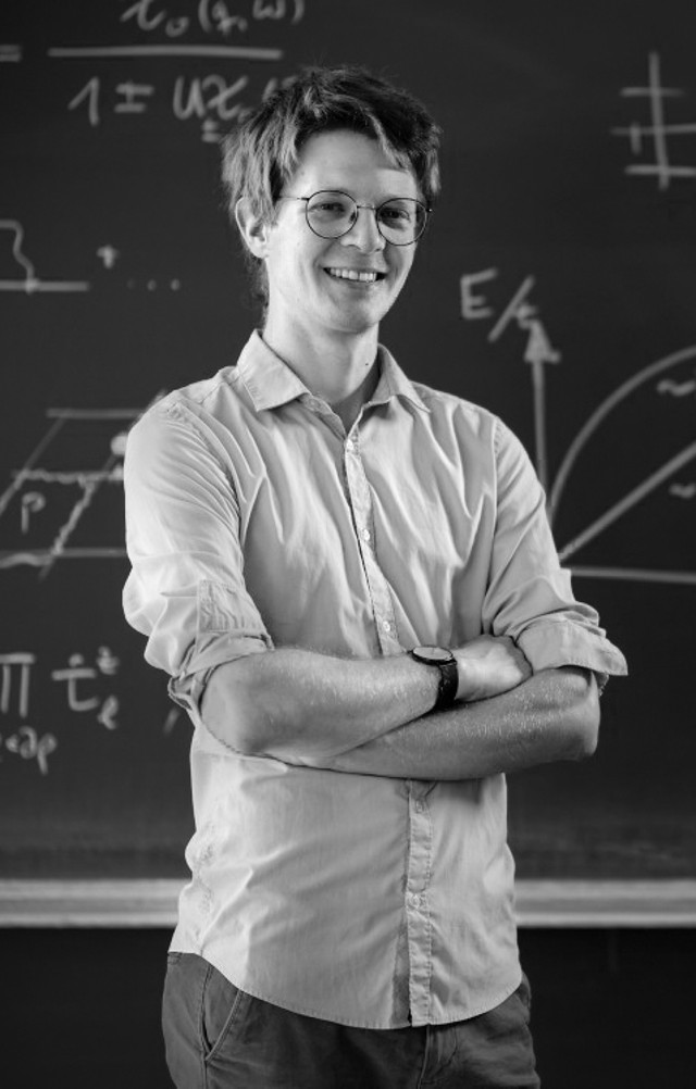 Fabian Grusdt standing in front of a blackboard filled with formulas.