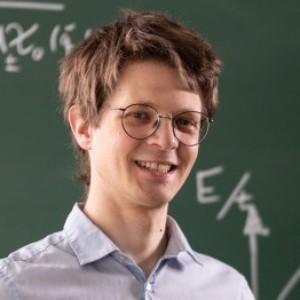 Fabian Grusdt standing in front of a blackboard filled with formulas.