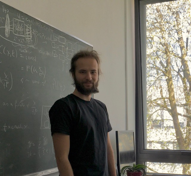 Alex Schuckert standing in front of a blackboard.