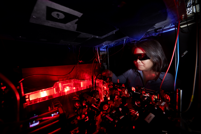 Female researcher working on a laser table top.