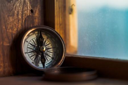 Open compass displayed on a wodden windowsill.