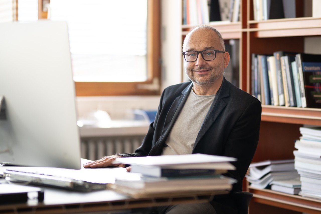 Prof. Ulrich Schollwöck sitting at his desk in his office.