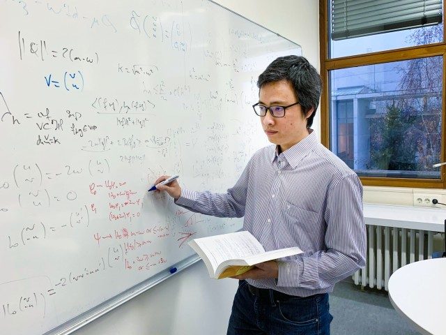 Phan Thành Nam writing mathematical formulas on a whiteboard in his office at LMU Munich.