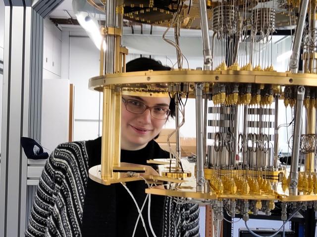 Nadezhda Kukharchyk in her laboratory standing behind an open cryostat.