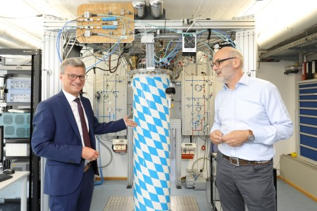 "State Minister Sibler (left) and WMI director Rudolf Gross (right) in front of a real ""Bavarian Quantum Machine""."